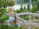 dziewczynka w ogrodzie na mostku oczka wodnego